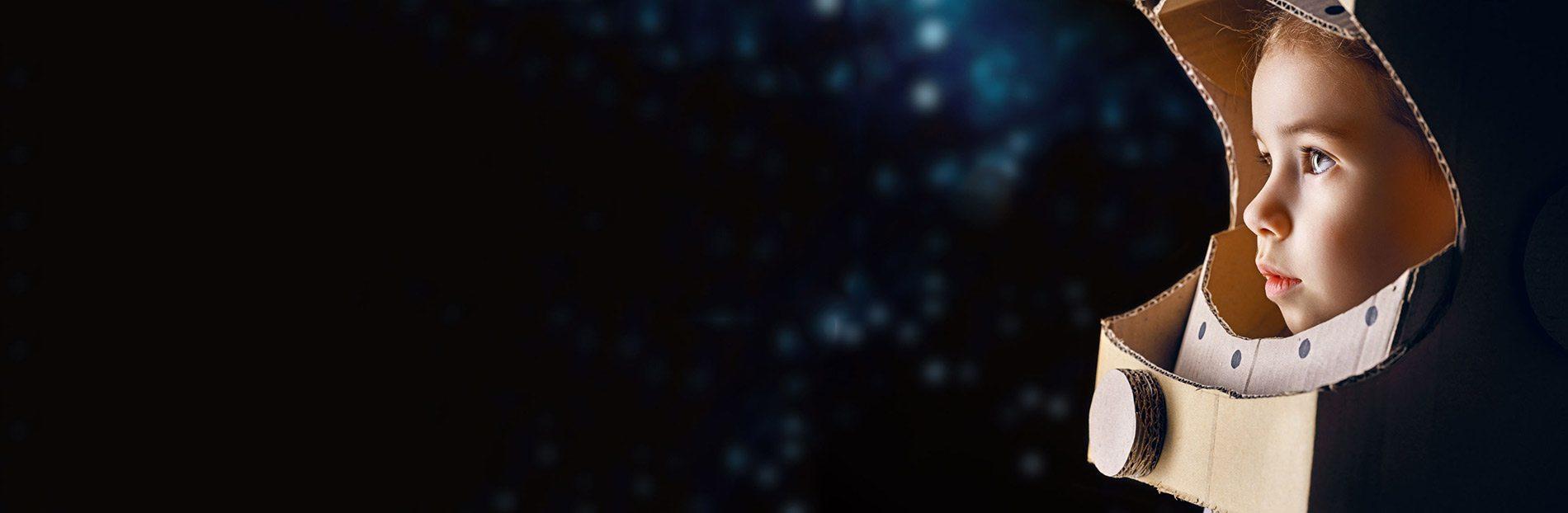 ילד עם קסדת אסטרונאוט עשויה מקרטון מביט לחלל בפליאה